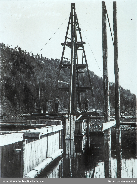 Fra byggingen av Sørlandsbanen. Ramming av hjelpepæler ved Lyselva (Ljosåna) bru ved km 303.78 mellom Herefoss og Hynnekleiv.