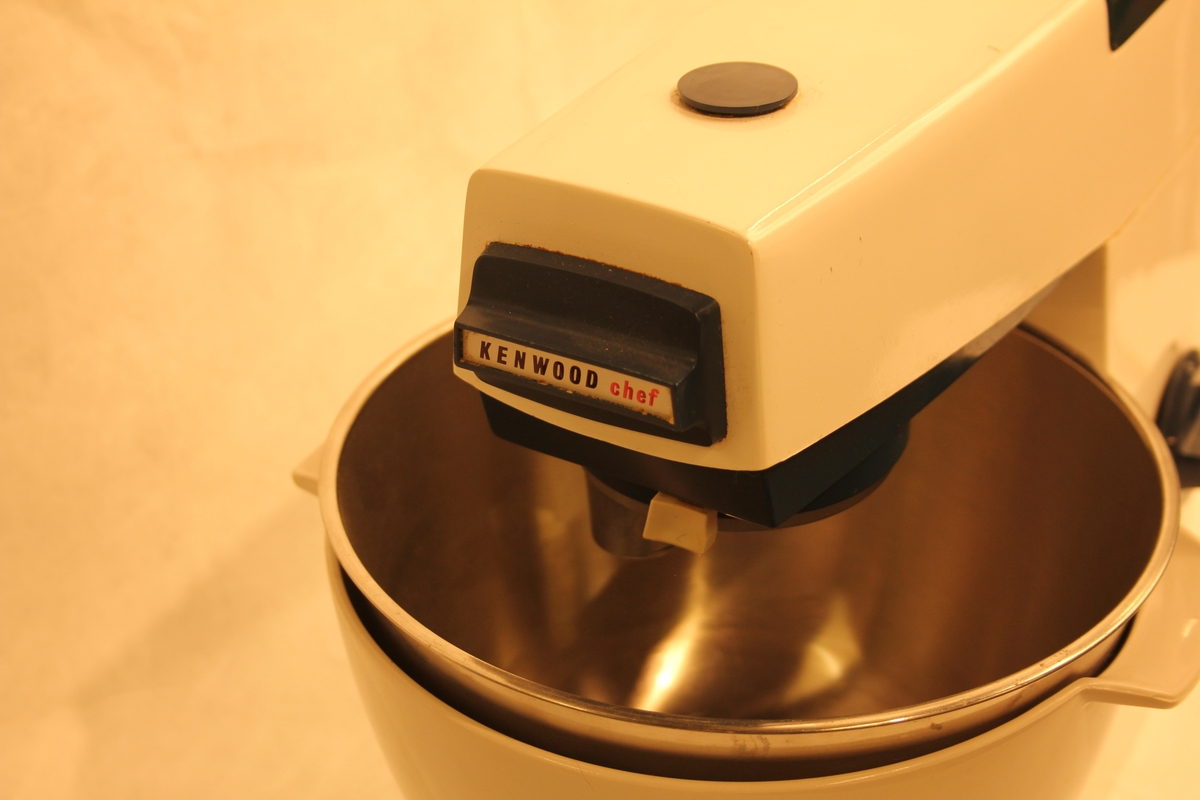 Kjøkkenmaskin med tilhøyrande bollar i plast og rustfritt stål. To vispar, den eine er noko øydelagd.