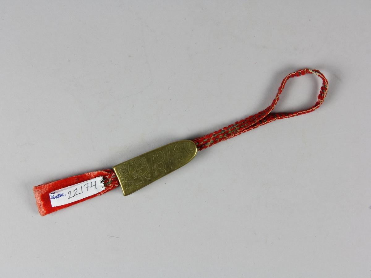Nålhus av mässingsplåt. Avlång klockformad med flata sidor. Genom mässingshylsan löper en ögla av ett mönstervävt band. Inne i hylsan sitter en lapp av ett dubbelvikt tjockt rött band med luggad yta. I  bandet kan nålarna fästas och sedan dras upp i hylsan av öglna. Hylsan är på båda bredsidorna dekorerad med ristad dekor. En signatur och årtalet 1818. Hylsan består av fyra delar som lödits ihop.