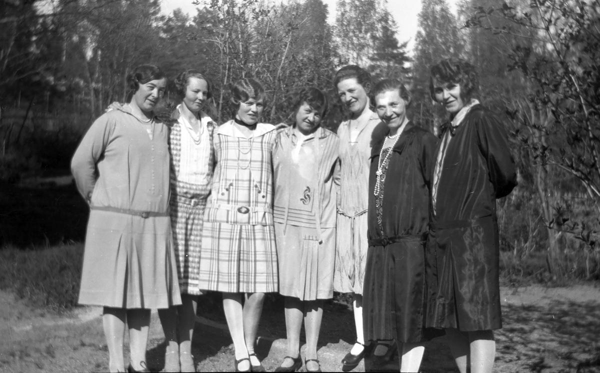 """Sju kvinner i """"tidsriktig"""" antrekk ute."""