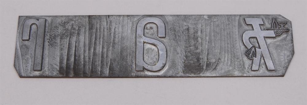 """Rektangulär kliché av silverfärgad metall. På ena sidan finns Trafikrestaurangers logotyp med bokstäverna """"TR"""" sammanlänkade i relief i form av """"TR-pojken"""". Logotypen kallas TR-pojken eftersom det ser ut som en person som håller armen i en serveringsgest. I ena armen håller TR-pojken en bricka med en flaska och ett champagneglas och över den andra armen, som vilar på höften, hänger en handduk. Efter logotypen följer bokstäverna: a och r, i relief. Mellan bokstäverna är det ett mellanrum."""