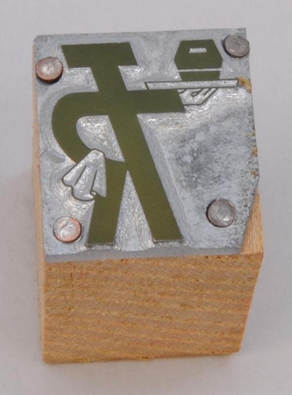 """Rektangulär kliché av silverfärgad metall, monterad på en träkloss. På finns Trafikrestaurangers logotyp med bokstäverna """"TR"""" sammanlänkade i relief i form av """"TR-pojken"""". Logotypen kallas TR-pojken eftersom det ser ut som en person som håller armen i en serveringsgest. I ena armen håller TR-pojken en bricka med en slags matlåda och över den andra armen, som vilar på höften, hänger en handduk. Logotypen är grön."""