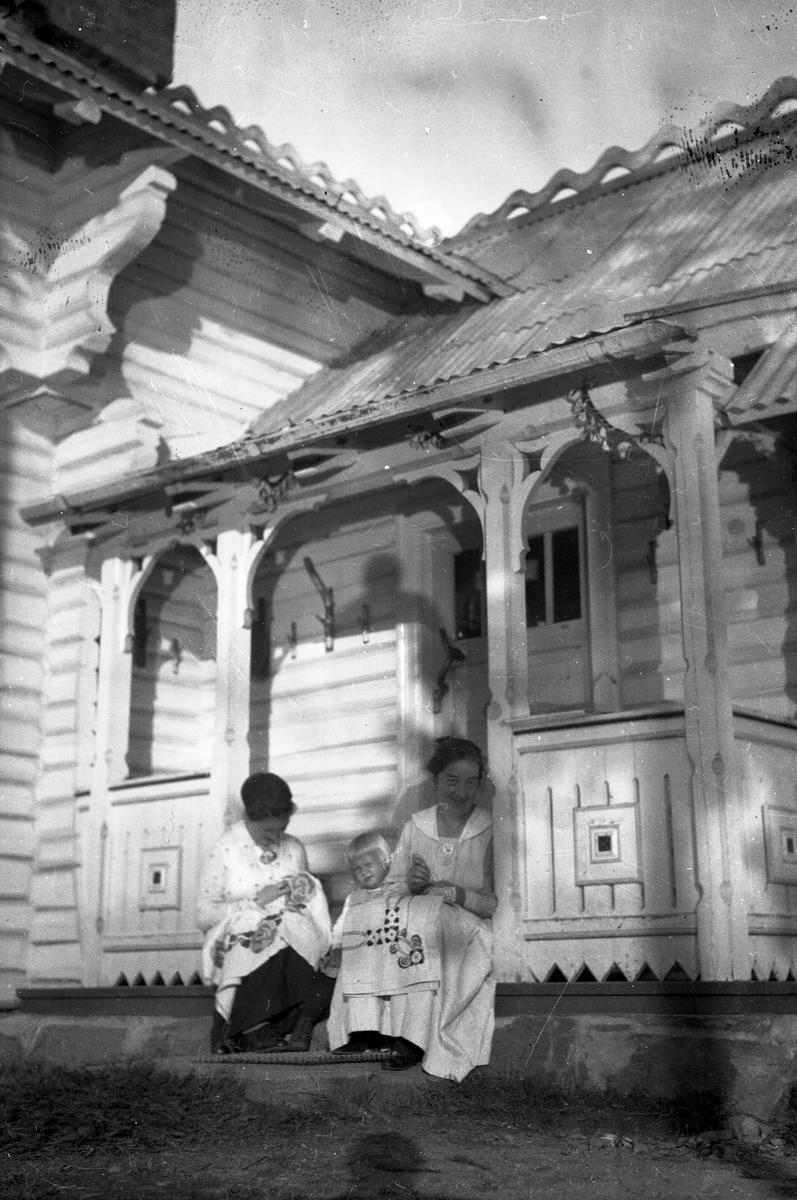 Broderende kvinner og ei jente sitter på trapa,Vester-Holm.