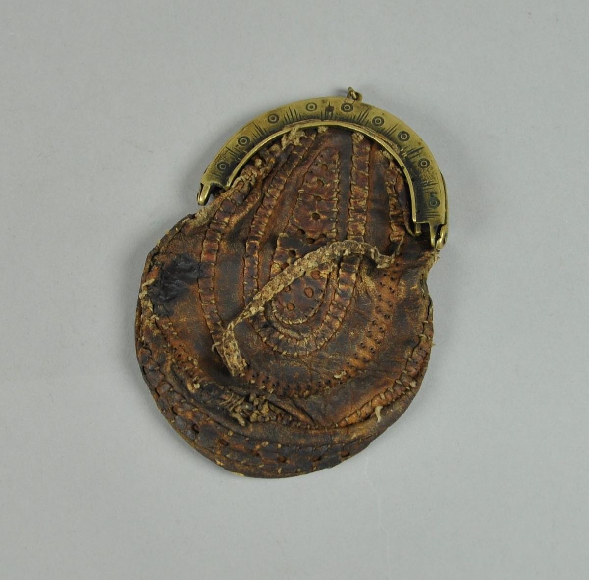 Pung av flettet skinn, med spenne av messing. På spennen er det inngravert dekor av sirkler og streker på tvers.