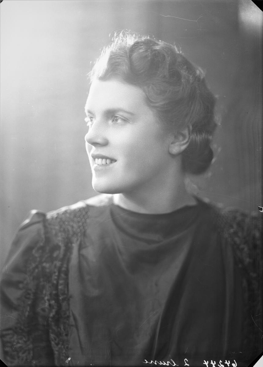 Portrett. Ung mørkhåret kvinne i mørk kjole med mønster fra skuldrene, ned ermene og langs siden. Bestilt av Aud Hermannsen. Koppervik