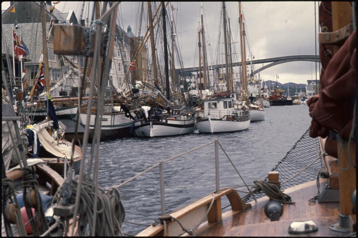 """Flere båter ligger på rad langs Indre kai i Haugesund under """"Havnedagene"""". I bakgrunnen ligger Risøybrua."""