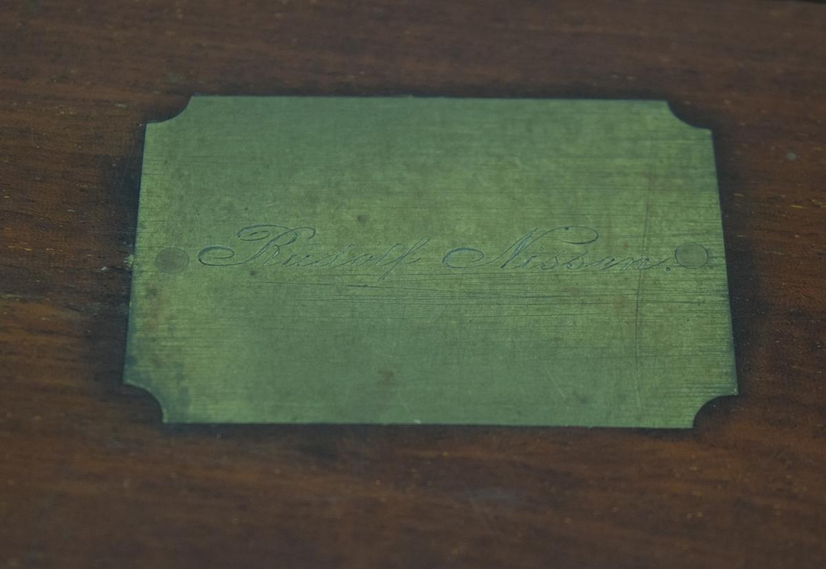 """Låda av fernissad mahogny för förvaring av sextant med tillbehör. Kvardratisk låda med lock, sinkade hörn. Handtag och hasp i mässing. Lås med sköldformad bas. Mässingsplatta på locket med gravering: """"Rudolf Nissen"""". Klädd med grön filtmatta invändigt, samt stöd av mahogny för alla tillbehör. Pappersettikett i locket: """"H. Hughes - Optical Nautical & Mathematical Instrument Maker, Fenchurch Street London."""". Ytterligare en lapp med texten: """"B. Cooke & son ltd Hull."""