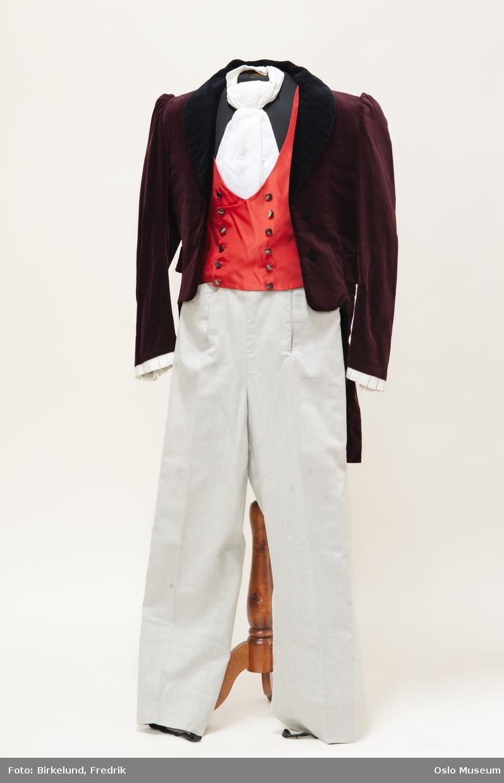 Hette i brun fløyel. Kantet med bånd i gull og sort. Foret med rødt tekstil i hetten og grå tekstil i delen som ligger over skuldrene.
