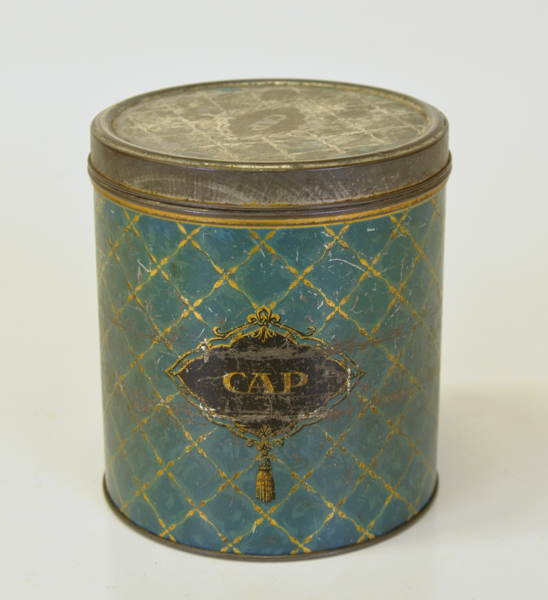 """Dekor i blågrönt och guld, färgen verkar ha bleknat. Text """"CAP"""". Lockets färg är bortnött.  Från Arne Ekströms handelsmuseum."""