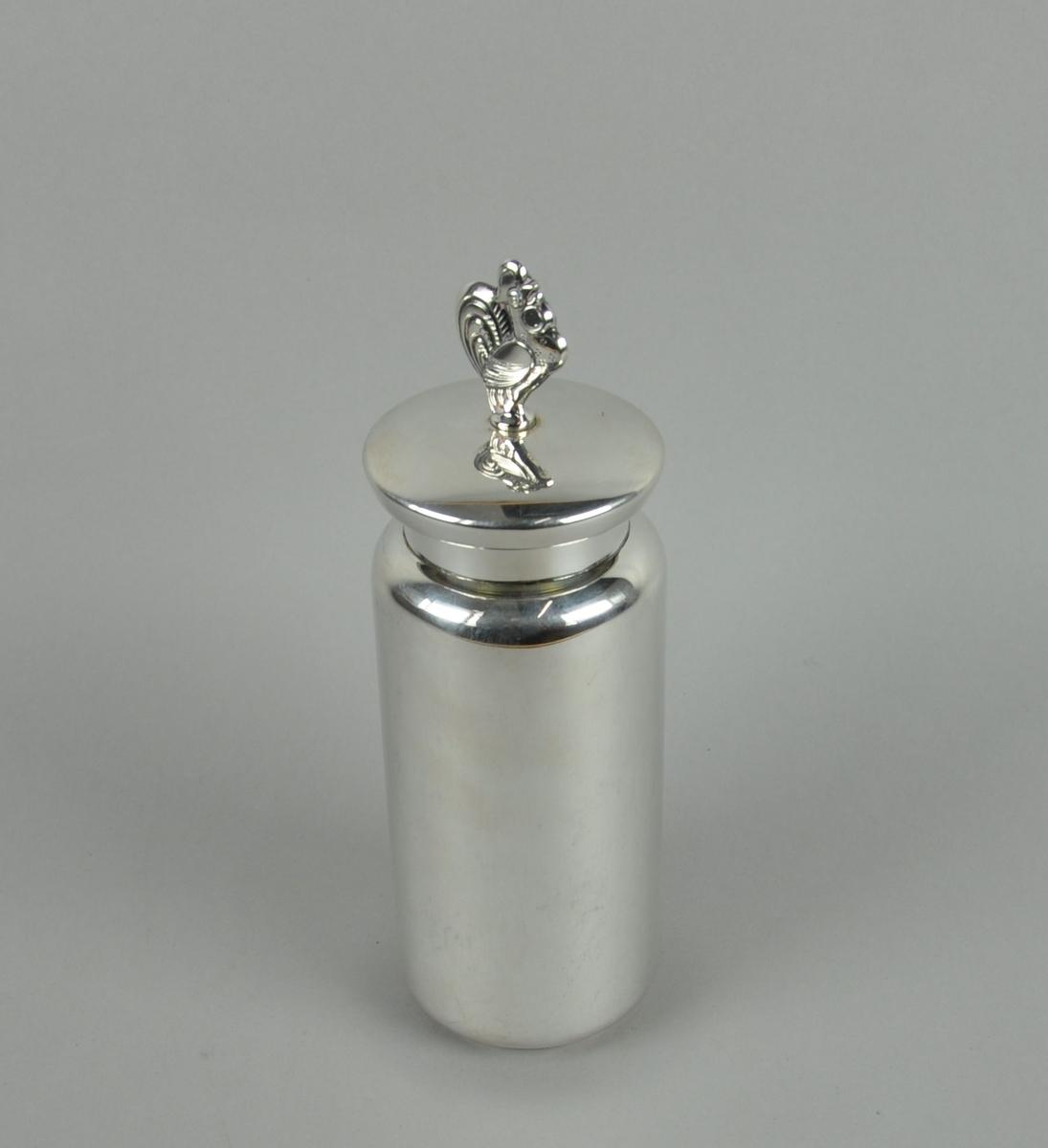 Coctailmikser av sølv. Har sylindrisk form med lokk. På lokket er det en knott som forestiller en hane.