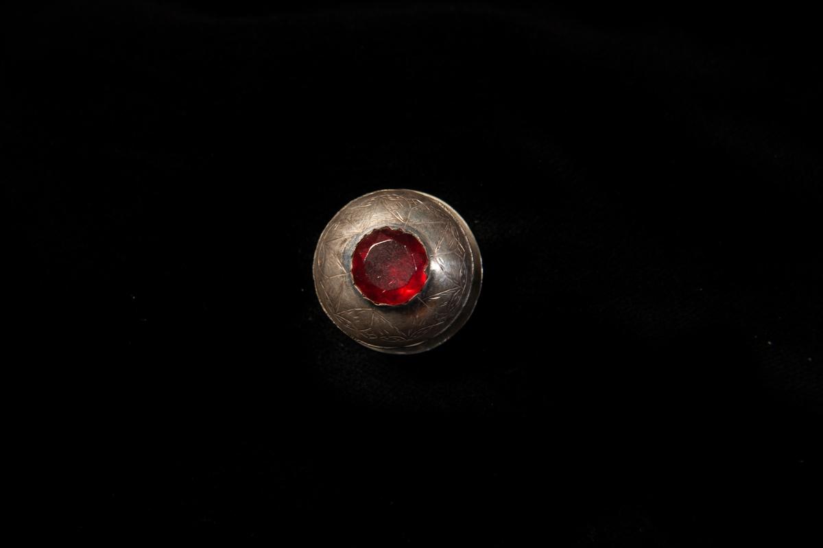 En stolpknapp i silver med graverad dekor i form av stiliserade blommor och blad. Infattad röd sten i glas. Något otydliga stämplar.  Jfr JM 8 072 och 8 073.