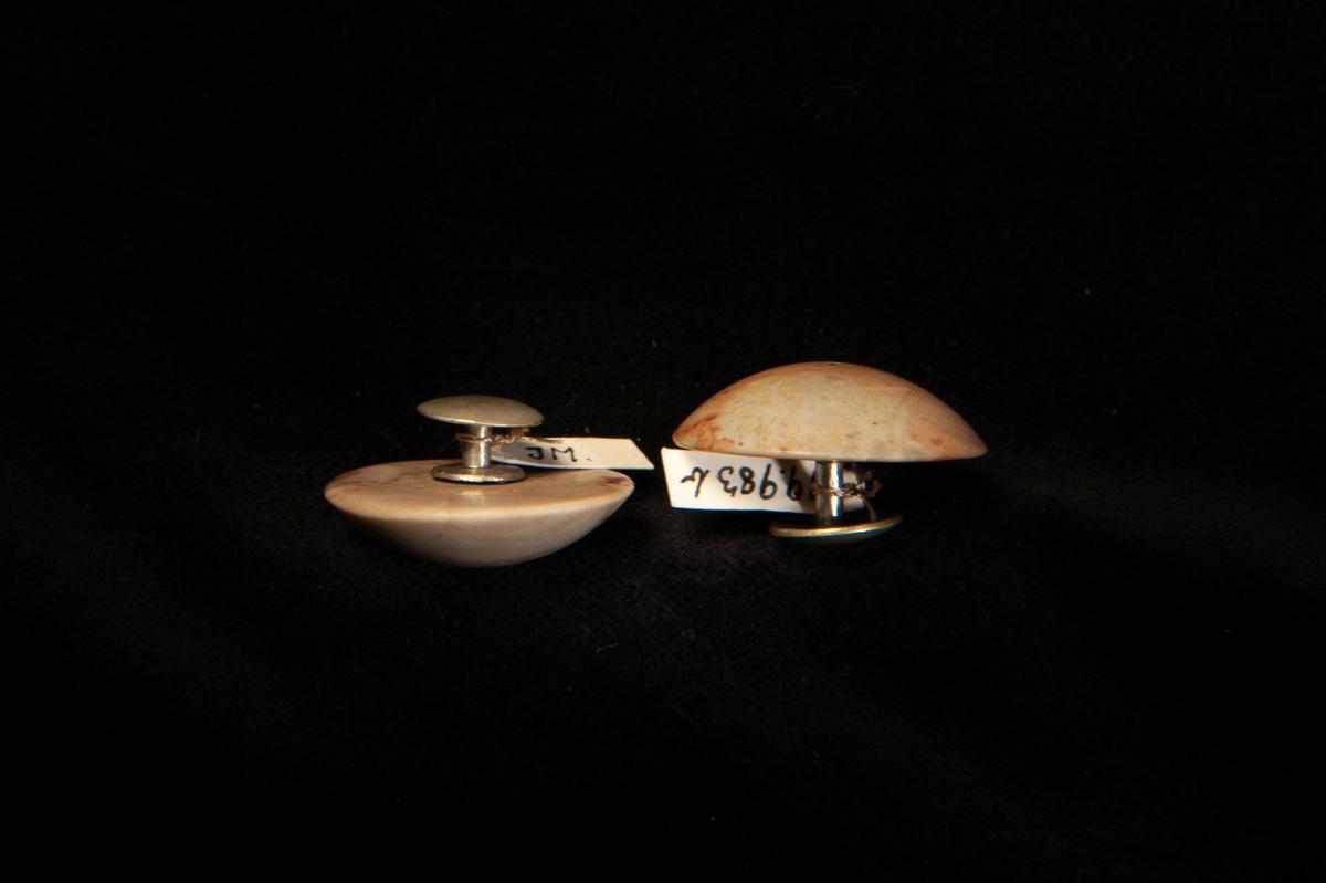 En enkel knapp av slipad ochpolerad brunbeige och vit agat. Fäste i vitmetall. Jämför med JM. 19983;a