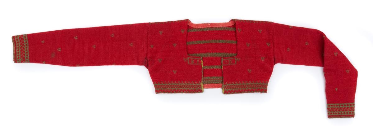Kvinnotröja, mönsterstickad på rundstickor i förenklad tvåändsstickning. Röd bottenfärg med mönster i grönt. Tröjan är uppklippt fram och inkantad med kattun. Grovt ylleband i fållningen nertill och vid halsen.