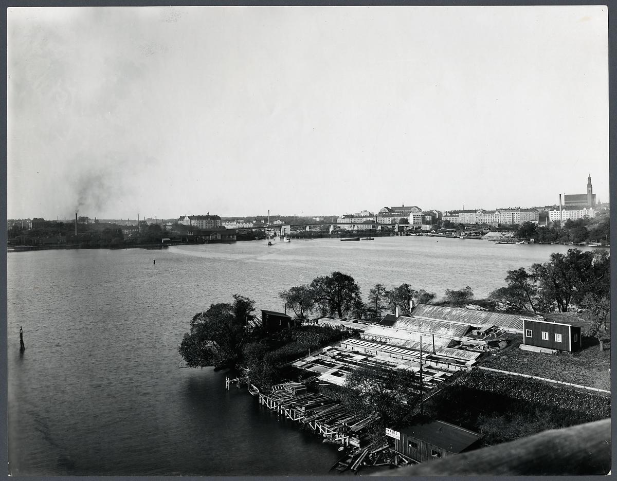 Vy över Årstaholmarnas trädgårdsodling från Årstabron. Liljeholmsbron i bakgrunden.