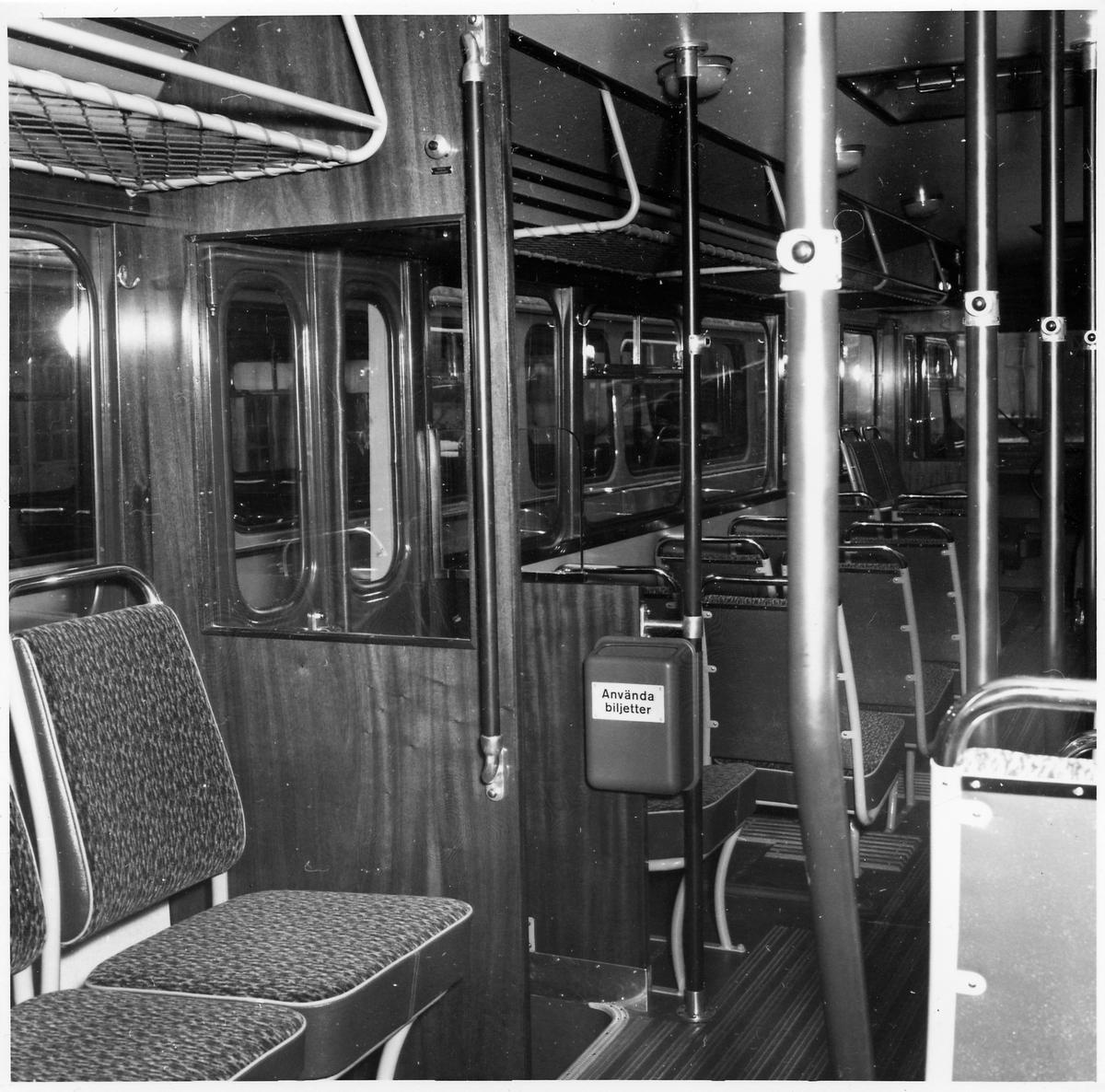 Interiör från en buss med sittplatser, stoppknappar och utgång.