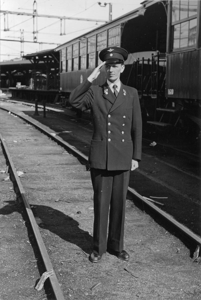 Okänd man i uniform framför Statens Järnvägar, SJ C4 1610.