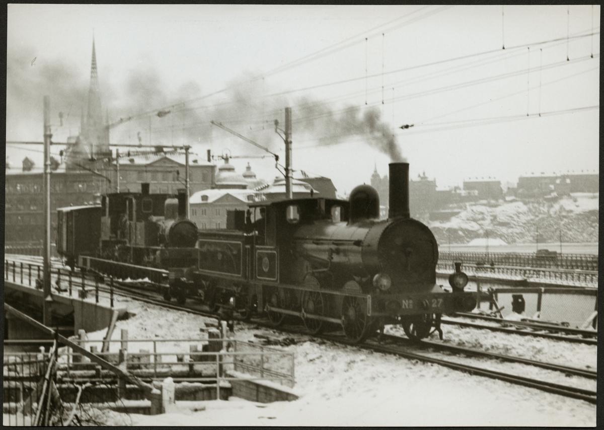 """Bergslagens Järnväg, BJ K 27 drar Gotlands Järnväg, GJ lok 3 """"Gotland"""" och Stockholm Roslagens Järnväg, SRJ lok 3 """"Rimbo"""" på transportvagn på linjen mellan Stockholm C och Norrström på parad 1 december 1956."""