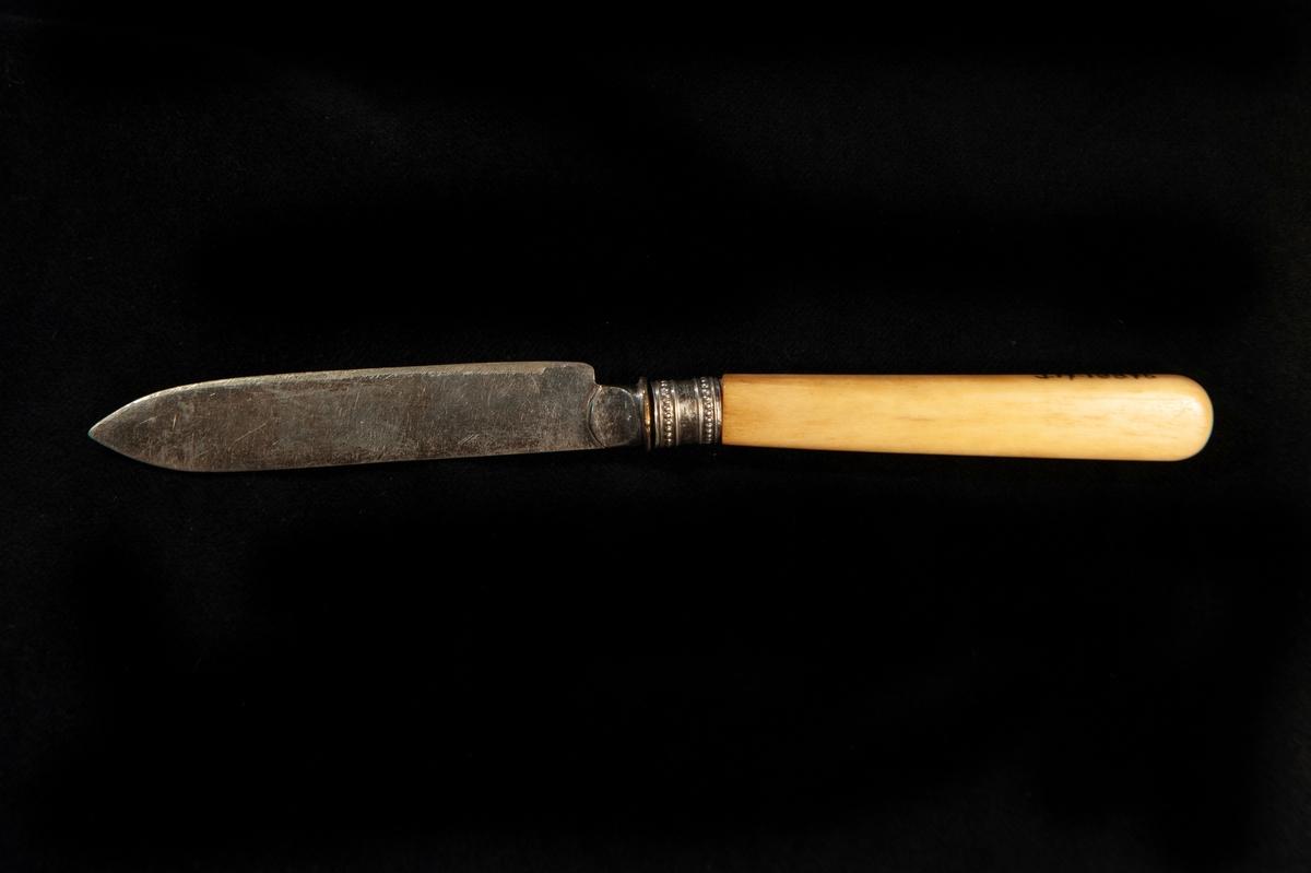En fruktkniv av silver/nysilver med skaft i gulbeige ben.  Dekor i form av zickzackbård på bladet. Otydliga utländska stämplar.   Jfr JM 18875 - 18878.