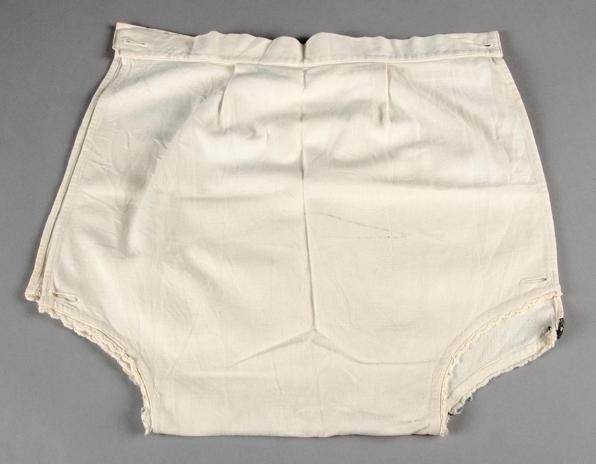 Underbyxor för barn av vit bomullslärft sydda i ett enda stycke med öppning i sidorna som knäpps i linningen och längst ned. påsydd linning fram och bak mot två lagda veck. Runt benkanterna påsydd spets.Fläckiga.