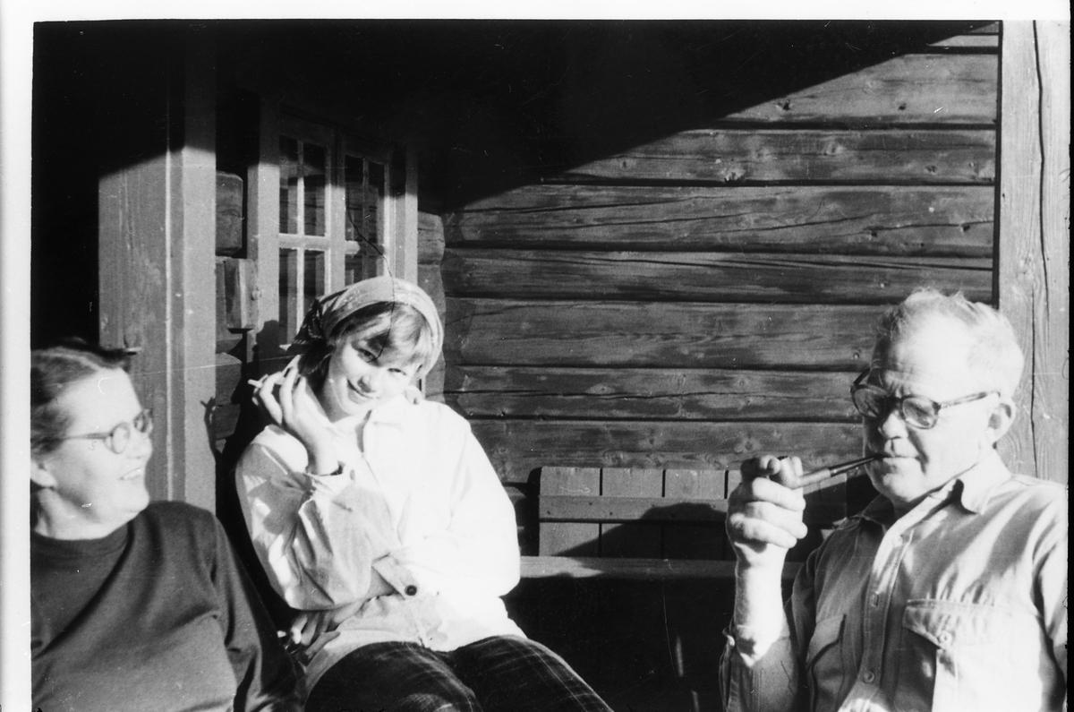 Avfotografert portrett av tre uidentifiserte personer, tilsynelatende ved en hyttevegg.