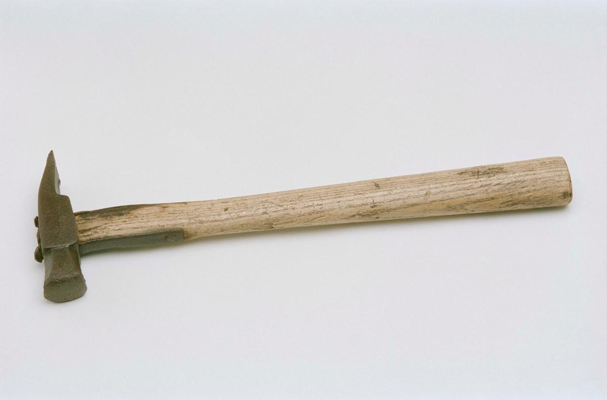 Hammare av järn med skaft av trä. Mellan huvud och skaft går två järnbleck som går ner en bit över skaftet. Användes till hästskoning.