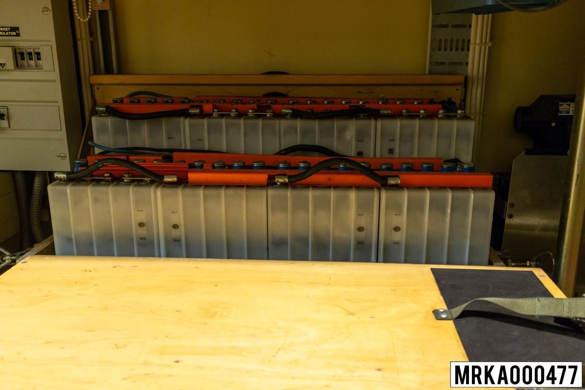 I ackumulatorlådor under manöverpanelerna finns åtta 6 V-ackumulatorbatterier. Under drift är dessa ackumulatorer seriekopplade och underhållsladdas från 220 V-systemet via likriktaren i strömförsörjningssystemet. Vid bortfall av inkommande 220 V-spänning lämnar ackumulatorerna 48 V-likspänning till strömförsörjningssystem 24 V, 48 V. Under transport levererar ackumulatorenra 24 V likspänning till transportvärmaren. De gaser (väte och syre) som bildas under laddning av ackumulatorerna, leds bort genom rör förbundna med en vetilationsöppning på kärrans högra sida. Strömförsörjningssystem 24 V, 48 V matas under normala drift med 220 V-växelspänning. Denna spänning likriktas, regleras och omvandlas till +24 V, -24 V och -48 V likspänning för strömförsörjning av sambands- och eldledningsutrustningar, nödbelysning samt underhållsladdning av ackumulatorbatterierna i ackumulatorlådorna. Vid spänningsfall matas strömförsörjningssystemet från ackumulatorbatterierna. Detta kan pågå under minst en halvtimma, sedan måste batterierna laddas om.  Övriga komponenter i strömförsörjningssystemet är likspänningsregulator, växelriktare, likriktare, likspänningsomvandlare och avstörningsfilter.  Ursprungsbenämning: ACKUMULATORLÅDA