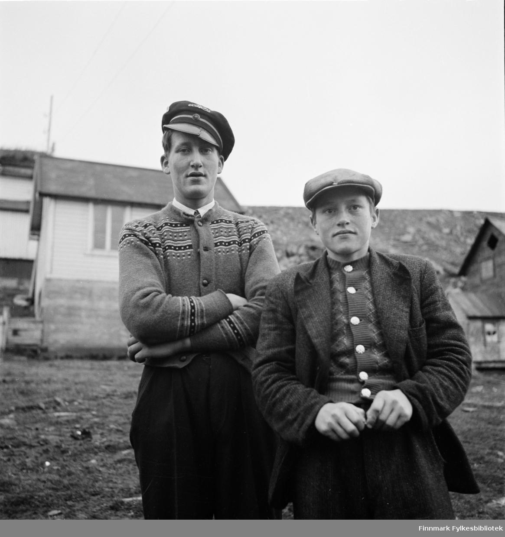 Kjøllefjord 1940. To unge menn avbildet i fine strikkejakker og skyggeluer. Til venstre: Dette er sannsynligvis Cato (Kato) Nilsen, sønn av fisker og båteier Eilert Isak Nilsen fra Kjøllefjord. Faren hans, Eilert er avbildet på et annet bilde;  FBib. 18010-033.  Cato jobbet for Televerket og iflg. vår informat er det Televerkets lue han har på hodet. Skyggen er sprukket, men reparert. Gutten til høyre er ukjent, også avbildet som skipper på en åpen båt med Sabb-motor: FBib. 18010-020. Det er tre bilder i serien med disse to unge menn.