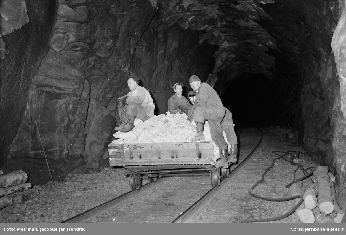 Steiner som er sprengt ut i forbindelse med strossingsarbeider er lastet over på tralle som her kjøres ut av Store Skiple tunnel mellom Reimegrend og Urdland stasjoner.
