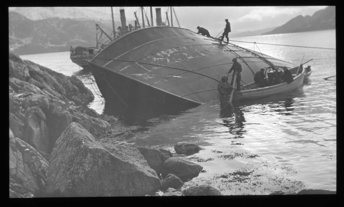 Berging av kantret skip fjæresteinene. Fire mann klatrer på skutesiden, liten lettbåt langs skutesiden.