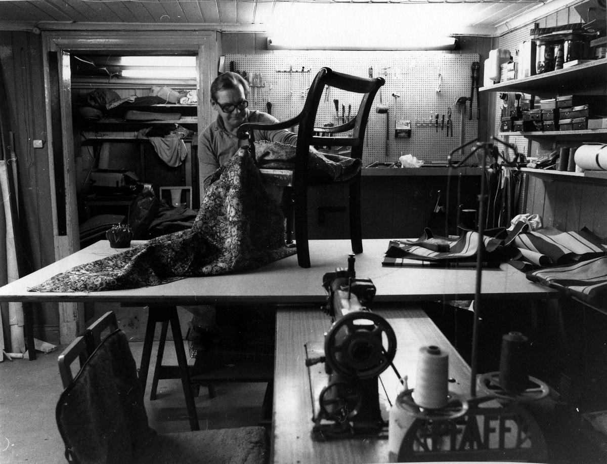 Alf Andersson på Alingsås Sadelmakeri & Tapetserarverkstad arbetar på en stol som står ovanpå ett större arbetsbord.