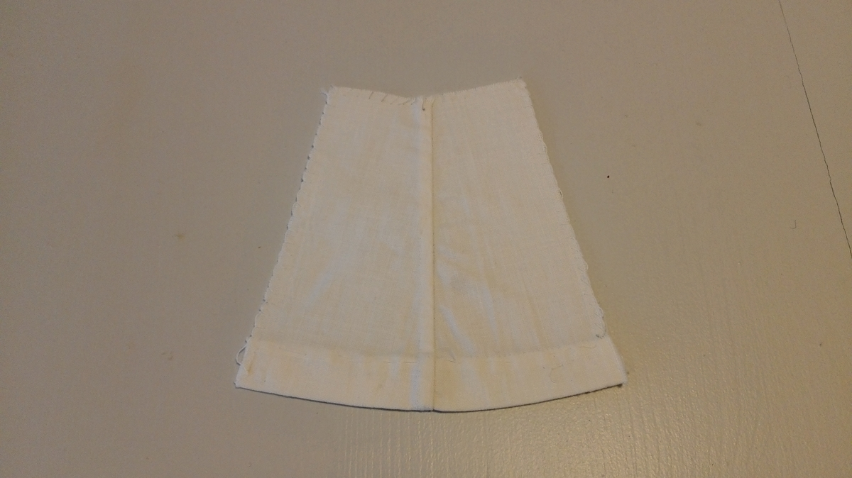 Form: M/fald og overkasta sårkantar. Prøve på fylgjande: Lagde saumar (sidesaum), overkasting, opplagd runda fald, tråkling (kjolefald). Sydd på middelskolen.