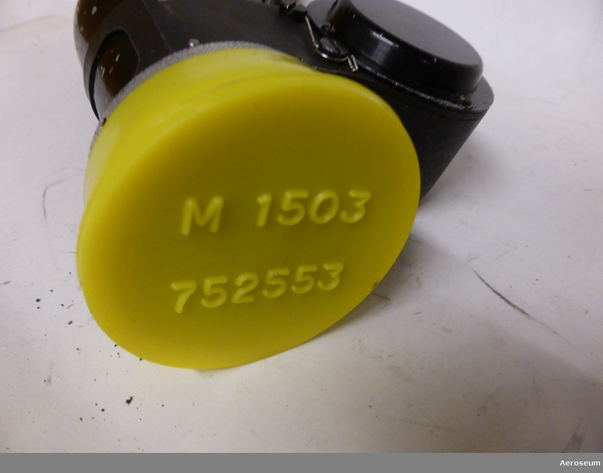 """Två stycken styrspakshandtag till J 35 (Draken). Gjorda i svart metall och bakelit.  På den ena spaken står det skrivet längst ner: """"BET F6400-017435"""", """"BEN STYRSPAKSHANDTAG"""", """"URSPR. BET SAAB-FD4-11"""", """"IND. NR 317"""". På en påklistrad lapp bredvid står det: """"CVA 801"""". Under detta går det att läsa: """"SAAB"""", """"STYRSPAKSHANDTAG FD4-11"""", """"68015 [går inte att tyda]"""", och """"TILLV. NR 317"""".  På den andra spaken står det allra längst ner: """"6800946 FD4-6 TNR 258""""  Båda styrspakarna har varsitt gult plastlock där det står """"M1503-752396"""" på den ena, och """"M1503-752553"""" på den andra."""