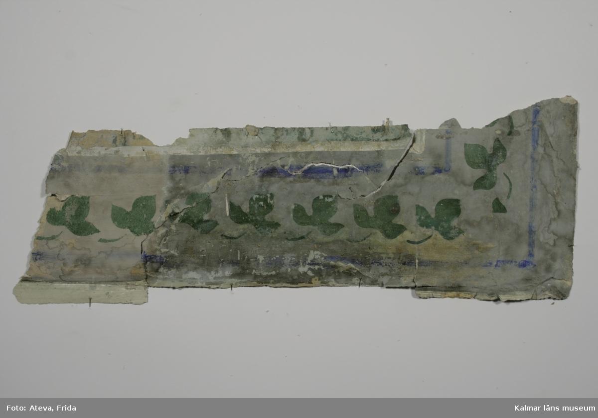 KLM 43769:2. Tapet, tapetbård. Av papper. Målad bård som tillhört målad tapet med marmorering i grönt och grått. De gröna bladen är schablonmålade i senare tid på 1800-talet. Bården i övrigt har grå botten och är från 1700-talet, liksom den målade tapeten som den suttit vid. Datering: 1700-1800-tal.