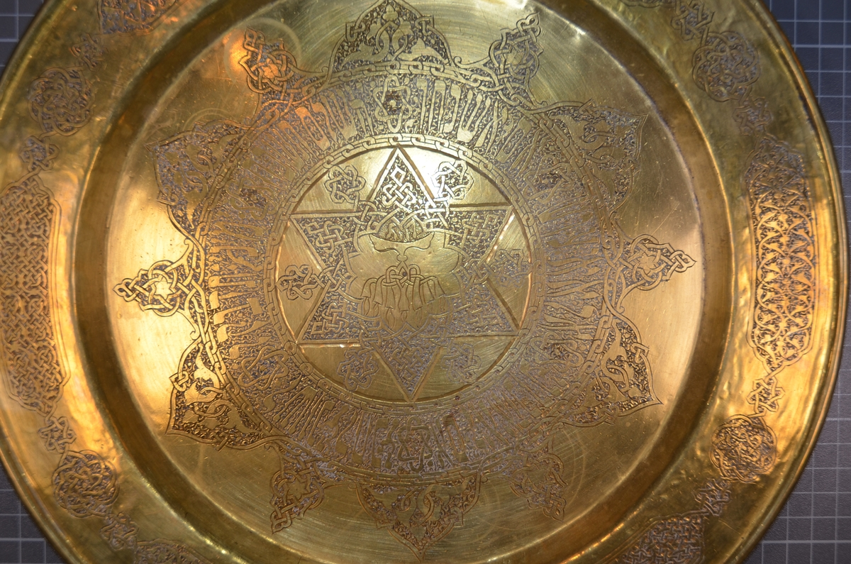 Kobber fat med inskripsjoner på hebraisk, samt spiralmønstret kant. I midten av fatet er avbildet Davidstjernen med en channukia i senter. Trolig brukt som serveringsfat utenom spesifikke høytider. Produksjonsdato ukjent.