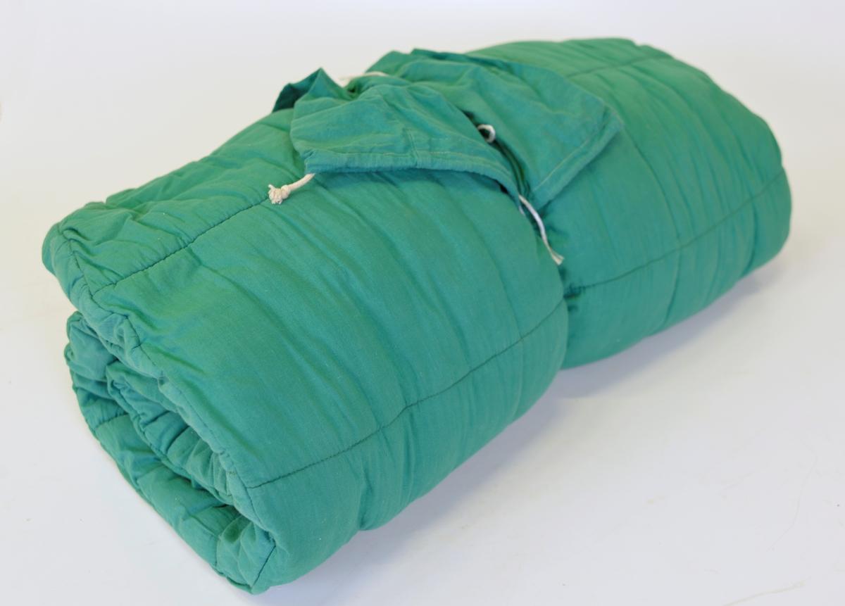 AM 1990:73:1: Grön vadderad sovsäck med en liten fastmonterad kudde och dragkedja på ovansidan.  AM 1990:73:2: Fodral Längd: 680 mm.
