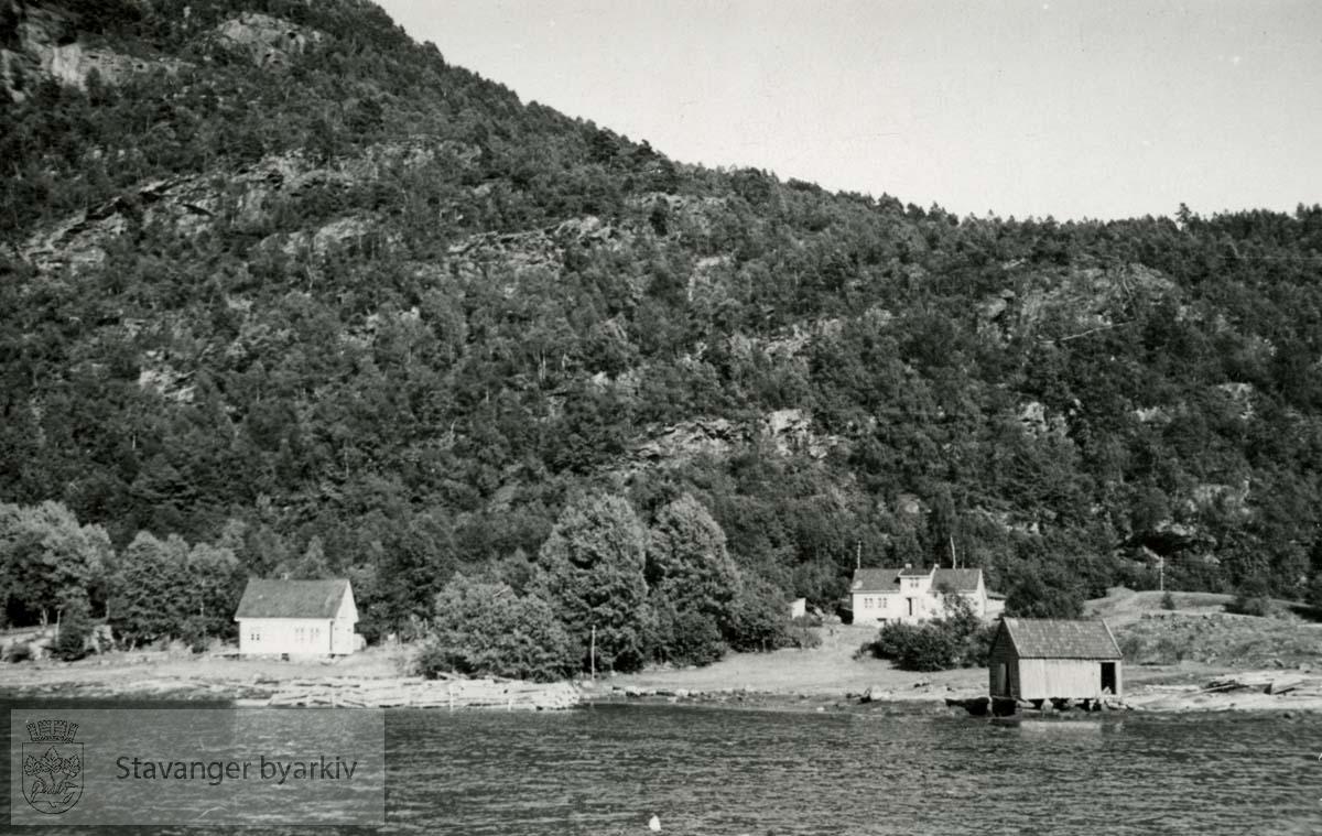 Små hus og båthus ved kysten , muligens Ryfylke