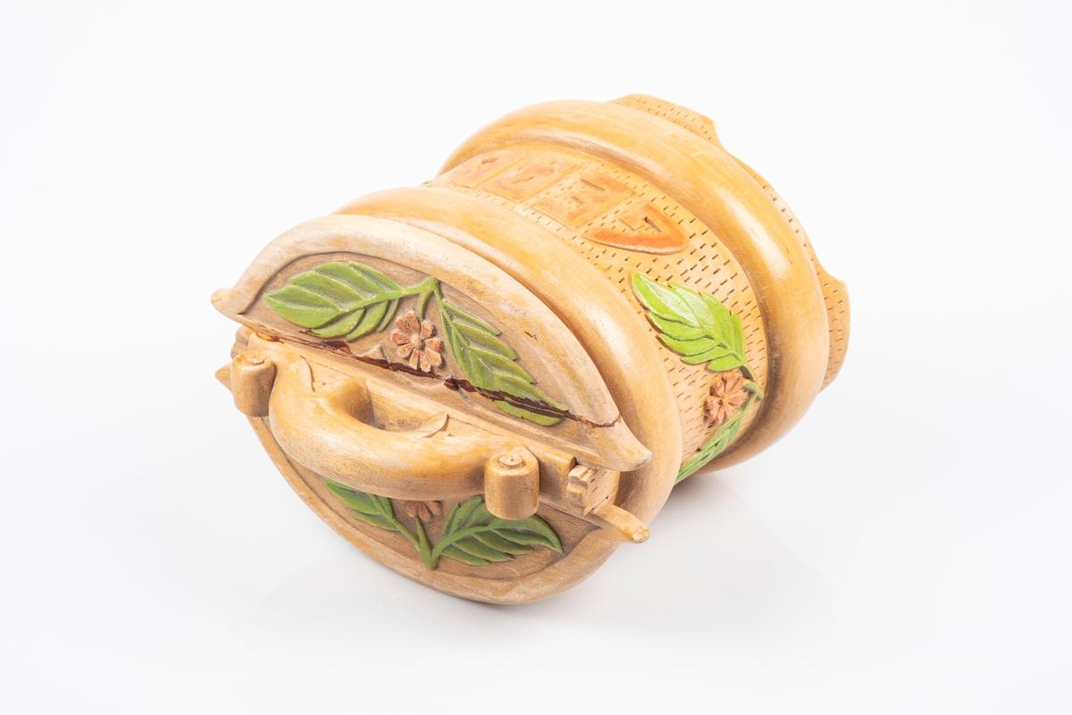 Ovalformet tine med lokk. Den er laget av tre. Det er utskjært blomstermotiver og tekst på tinen. Håndtaket på lokket og bunnen av tinen er limt på.