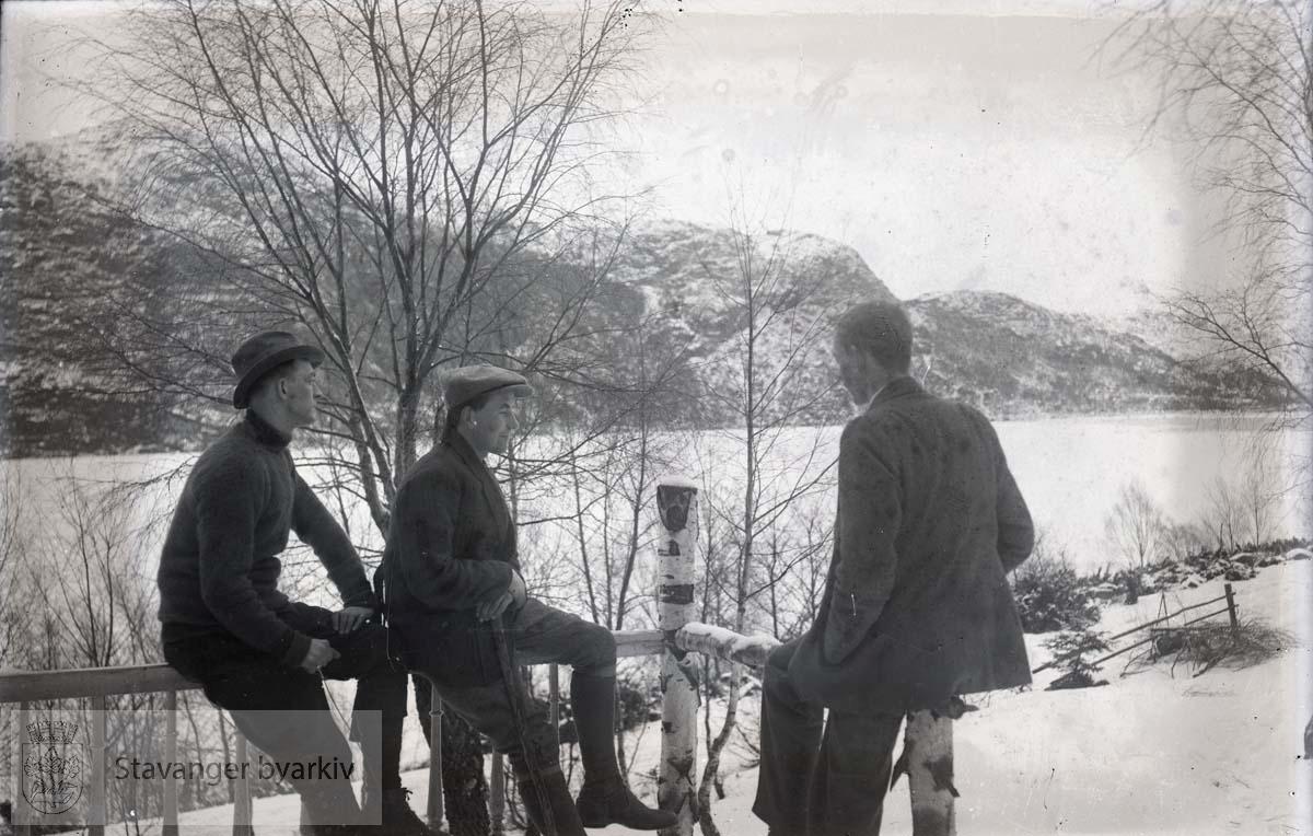 Tre menn i landskap ved fjord