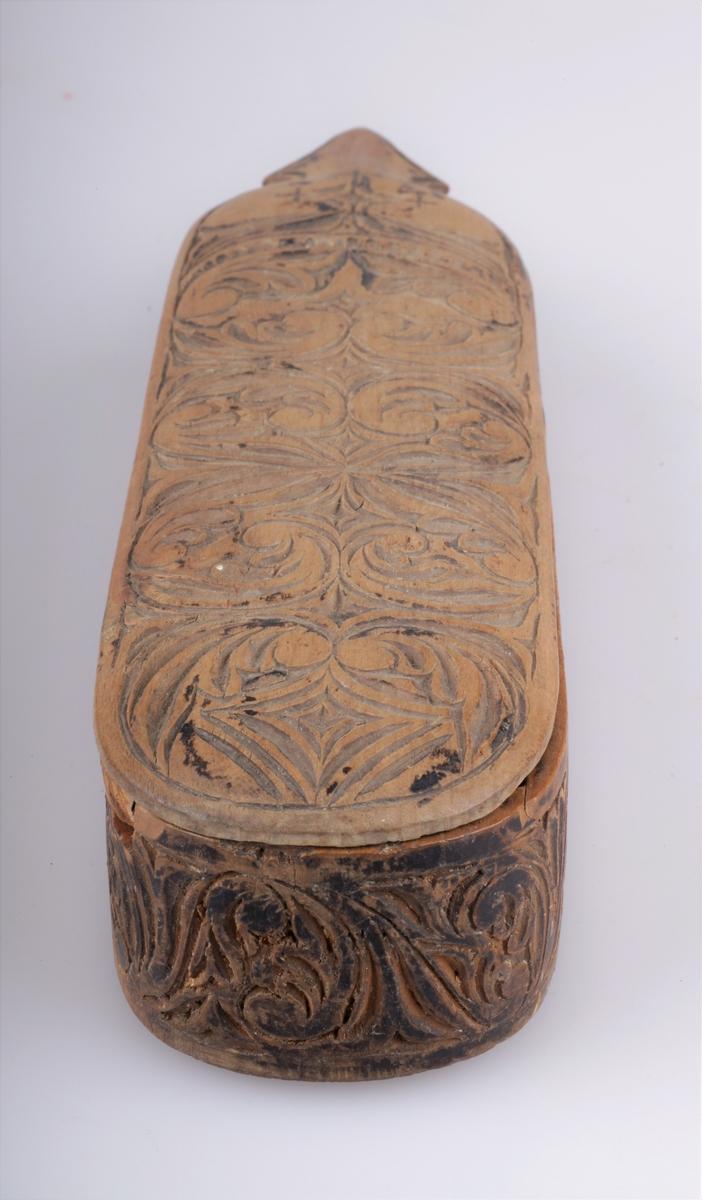 Barberskrinet er umalt, skyvelokk rikt utskåret på sider og lokk.