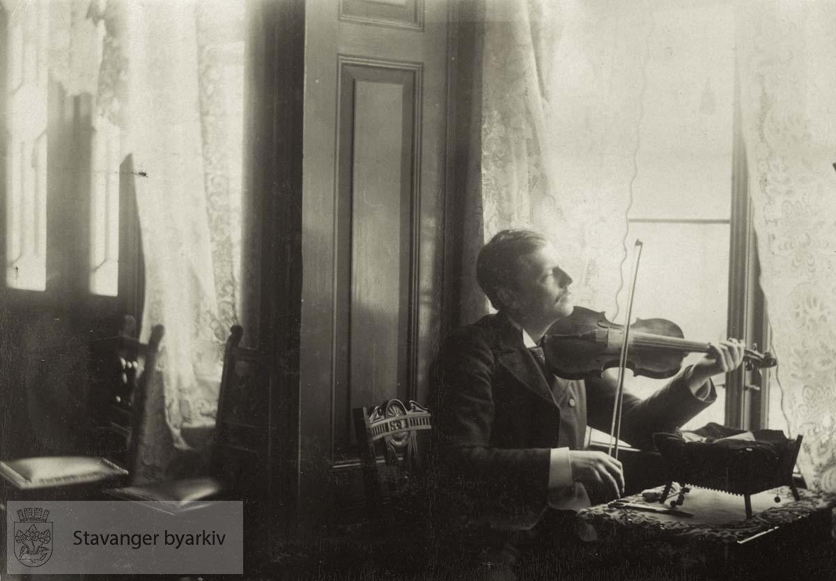 Georg T. Monsen trakterer fiolin i stua i Lilledal