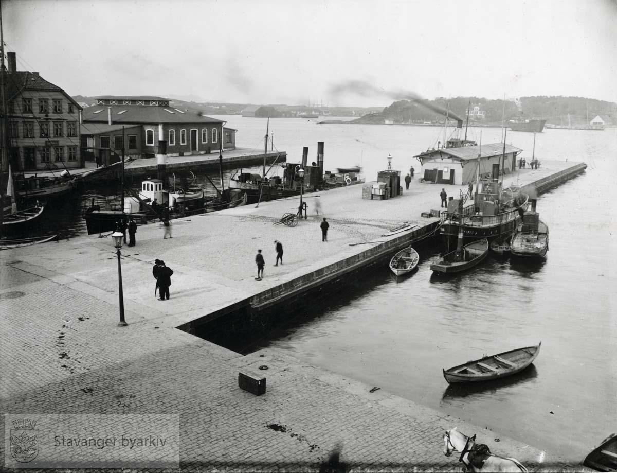 """Østervåg havn mot nord. Båter, bl.a. """"Sigurd"""" og """"Strand"""", liggende til kaien. Kjeringholmen med slakthuset til venstre. Sølyst til høyre i bakgrunnen."""