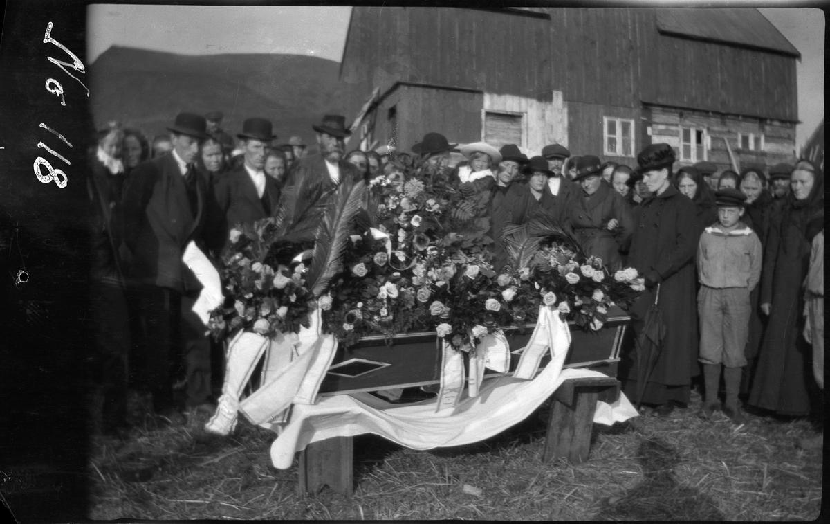 Blomsterprydet båre på et gårdstun. Begravelsesfølget står bak.