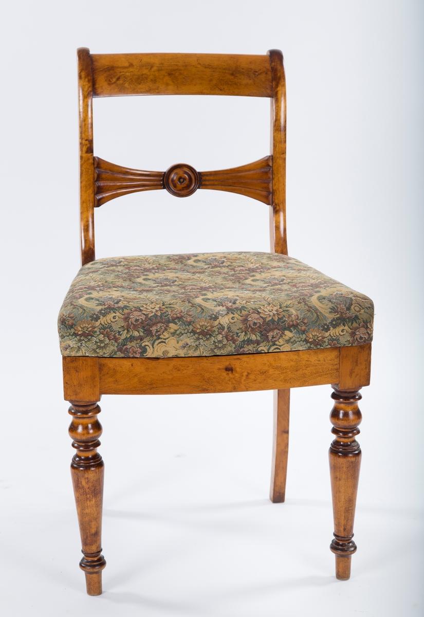 Spisestuestoler uten armlener. Løse seter med stopp, og trekk med blomster og mennesker. Setestoffet er spikret fast til stolrammen. Tegn på at setene er trukket om. på undersiden kan man skimte et annet tektstil i en lilla og rosa farge. En tapp i rammen og et hull på undersiden av setene holder dem på plass. Dreide stolben foran og utstkjæringer i ryggen. Svak bøy på stolbena bak. Tverrbrett med innfelt rosett. Biedermeierstil.   Noen av stolene viser tegn til reparasjon. Tappen som stikker ut øverst til venstre på stolryggen på stol II og III ser ut til å ha blitt limt på. Det samme gjelder stol V, men tappen på høyre side. På stol II er det et rent kutt.