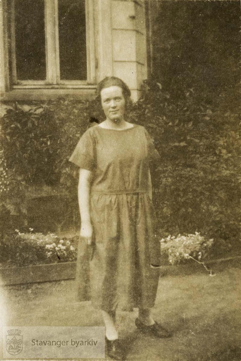 Kvinne i mørk kjole foran murhus
