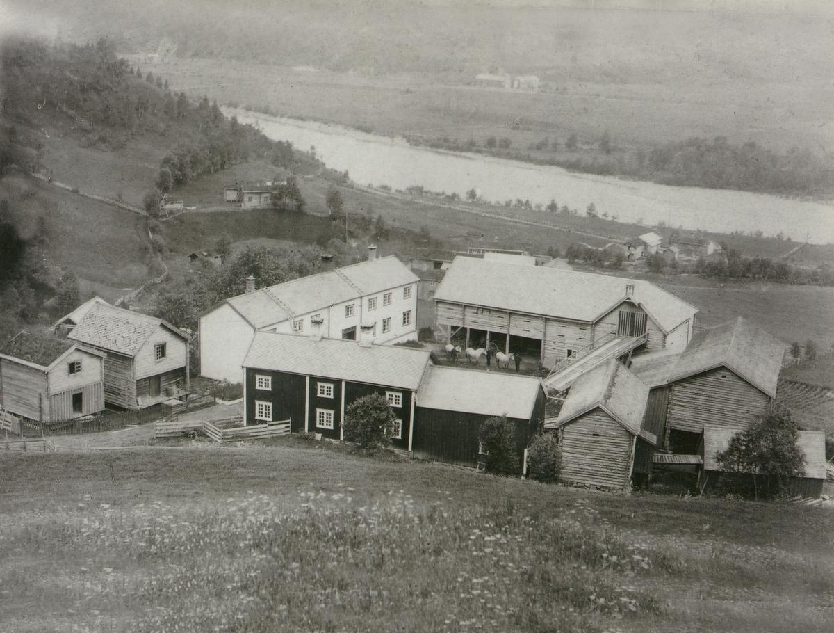 Gårdstun med våninghus og mange uthus. Utsikt mot Gaula.