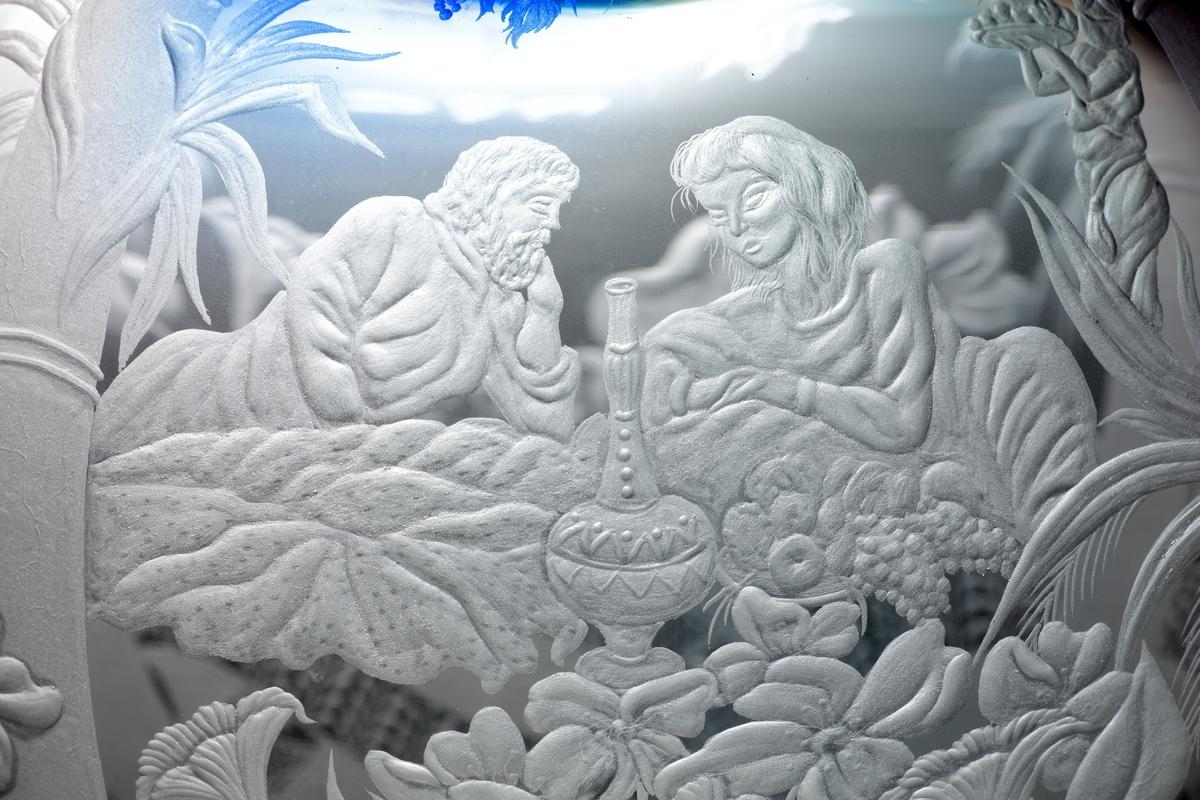 Fyrkantig glassockel. Droppformad skulptur som avslutas med en slipad knopp. I knoppen gröna och blå linjer. Skulpturen graverad med detaljerat motiv från Edens lustgård.