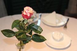 Pyntet bord med rose i forkant og kaffeservice i bakgrunnen
