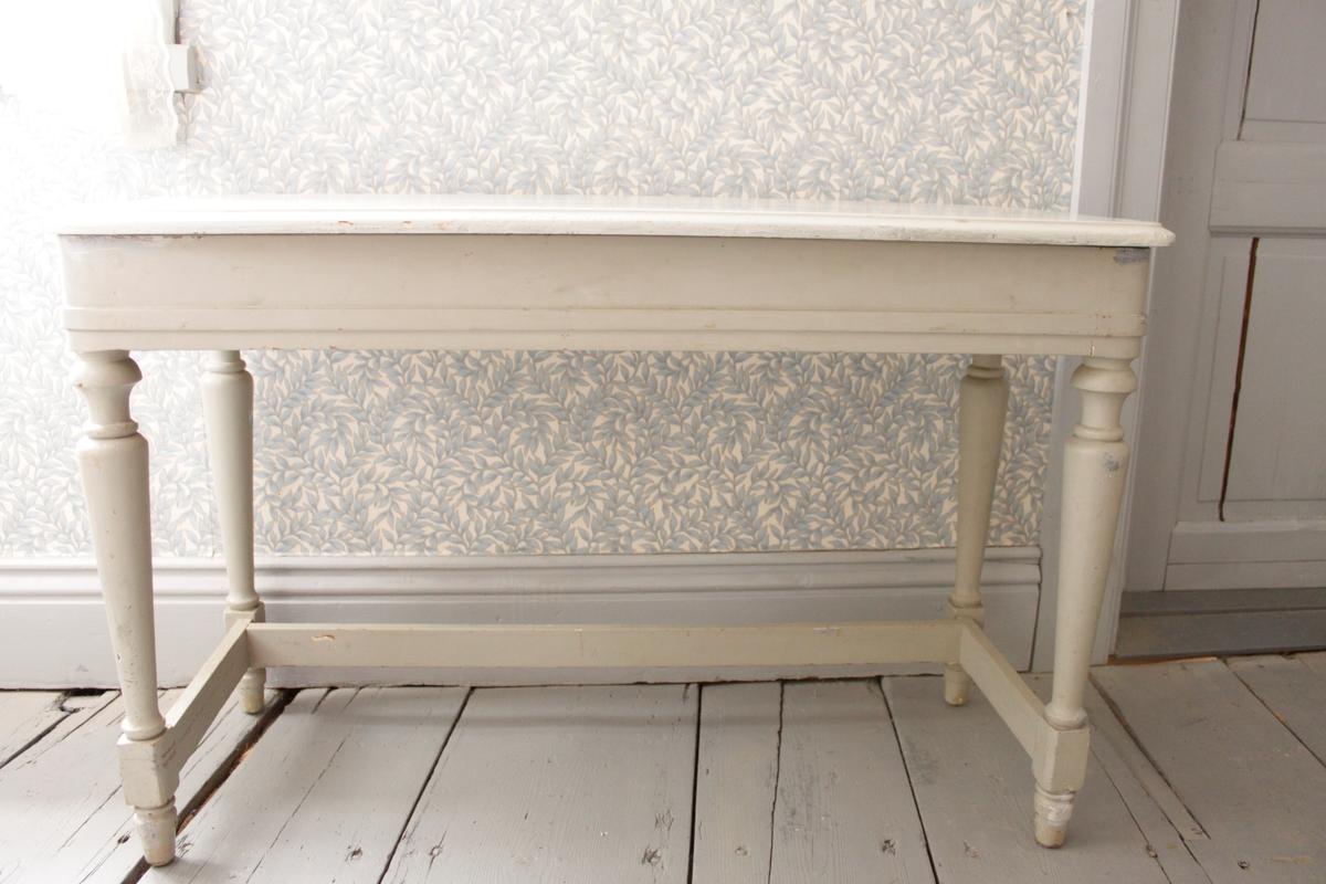 Lågt gråmålat bord med svarvade ben och tre tvärslåar mellan benen. Med en uppfällbar bordsskiva som döljer en låda i bordets sarg.