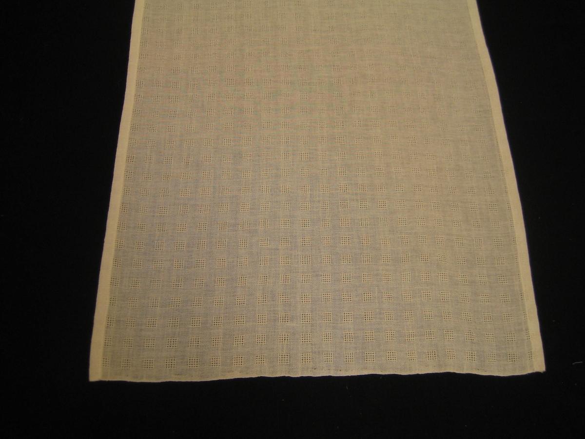Gardin med vit bomull i varp och inslag med myggtjällsrutor. Rutorna 1,1 cm breda och över 15 trådar och är placerade med 1 cm mellanrum.