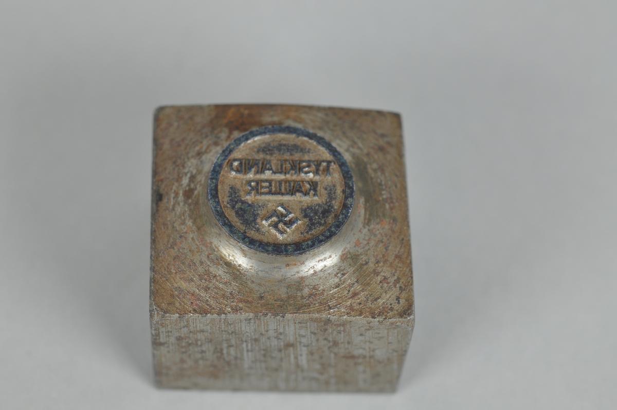 """Et rundt stempel med tekst """"TYSKLAND KALLER"""" speilvendt og hakekors-symbol i metall. Stempelet er preget av rust."""